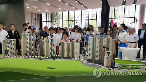 This photo, taken on Aug. 20, 2016, and provided by Doosan E&C, shows a group of people looking at a miniature of a new apartment complex to be built in Seoul before they place their bids to purchase the new apartment units. (Yonhap)