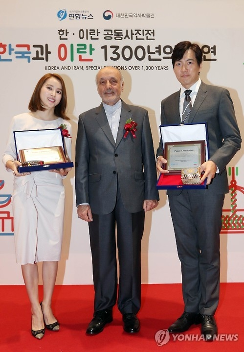 Iranian Ambassador to South Korea Hassan Taherian (C) presents plaques of appreciation to South Korean actress Han Hye-jin and actor Song Il-gook in recognition of their contribution to the development of bilateral ties. The awarding ceremony took place on the opening night of the special photo exhibition at the National Museum of Korean Contemporary History in Seoul on Sept. 28, 2016. (Yonhap)