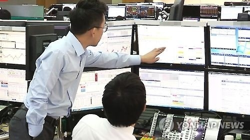 Stock brokers in Seoul monitor share prices in this undated file photo. (Yonhap)