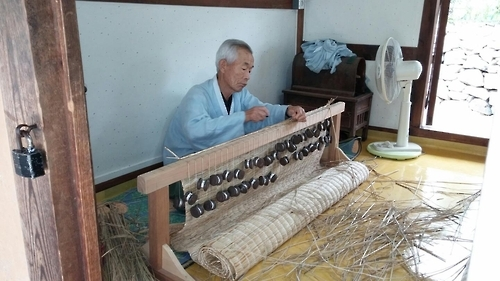 An elderly man weaves a straw mat at the Haemieupseong Festival on Oct. 7, 2016. (Yonhap)