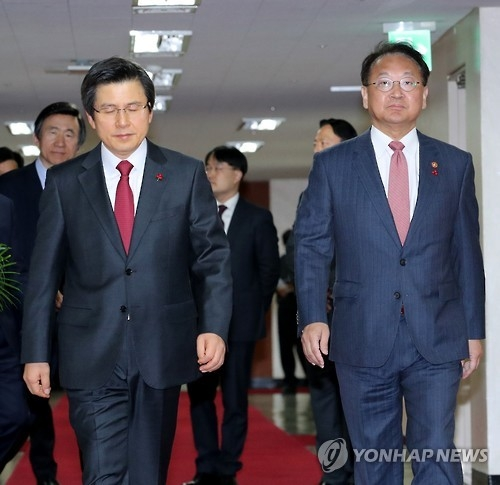 Acting President Hwang Kyo-ahn (L) walks with Finance Minister Yoo Il-ho (R) at the Seoul Government Complex on Dec. 13, 2016, to attend the Cabinet meeting. (Yonhap)