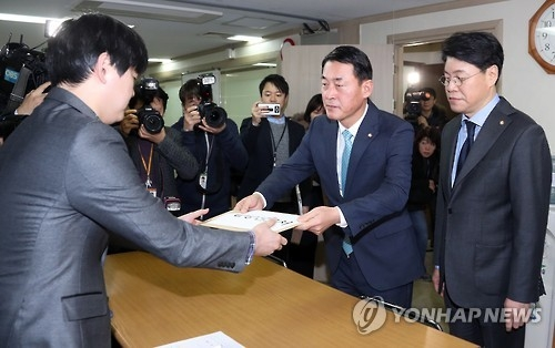 Dissenting faction members of the ruling Saenuri Party hand in resignation forms at the party headquarters in Seoul on Dec. 27, 2016, formally announcing their departure. (Yonhap)
