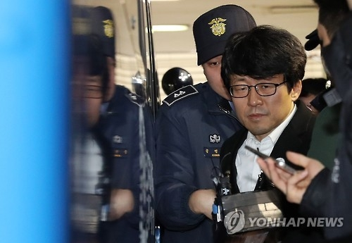This photo, taken on Dec. 31, 2016, shows Ryu Chul-kyun, a professor of Ewha Womans University, being escorted by police in Seoul to face questioning by the independent counsel team investigating a corruption scandal involving President Park Geun-hye and her friend. (Yonhap)