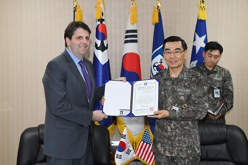 In this photo taken on Jan. 9, 2017, and provided by the Navy, U.S. Ambassador Mark W. Lippert (L) and Republic of Korea Fleet Commander V. Adm. Jung Jin-sup pose for a photo after the top U.S. envoy was named as honorary member of the ROK Navy in southern port city of Busan. (Yonhap)