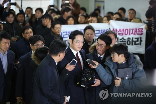 Samsung Electronics Vice Chairman Lee Jae-yong (C) is surrounded by reporters as he arrives at the investigation team's office in southern Seoul on Jan. 12, 2017. (Yonhap)