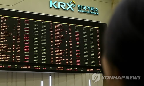 A stock investor monitors share prices on an electronic board at the Korea Exchange in this undated file photo. (Yonhap)