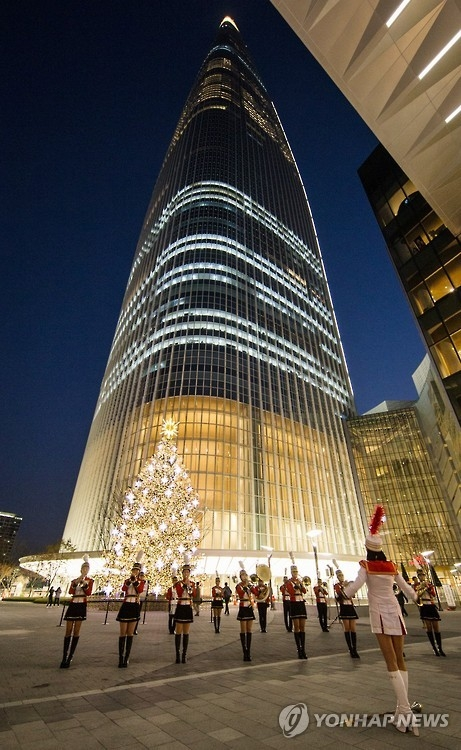 This file photo provided by Lotte on Nov. 4, 2016, shows a marching band playing a Christmas carol the previous day in front of Lotte World Tower. (Yonhap)