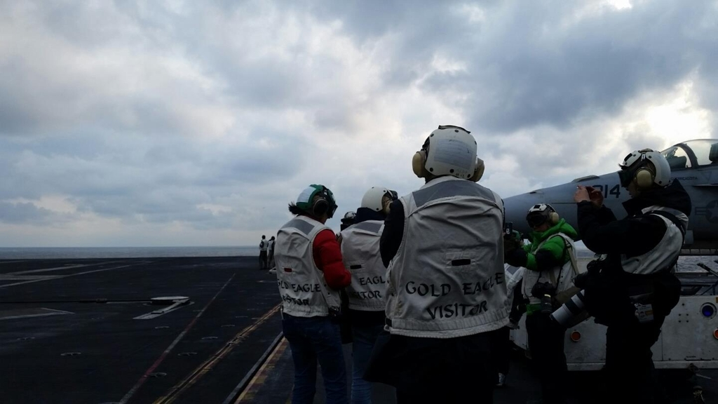 In this photo taken on March 14, 2017, reporters wait for an aircraft to take a picture of the moment of its landing on the deck of USS Carl Vinson in the East Sea. (Yonhap)