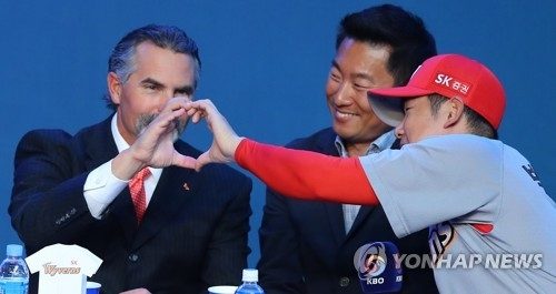 Trey Hillman (L), manager of the SK Wyverns, forms a heart with his pitcher Park Hee-soo during the annual Korea Baseball Organization media day in Seoul on March 27, 2017. (Yonhap)