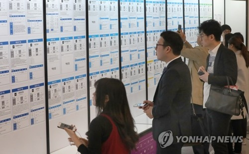 Job seekers look at hiring advertisements at a job fair in Seoul on April 20, 2017. (Yonhap file photo)