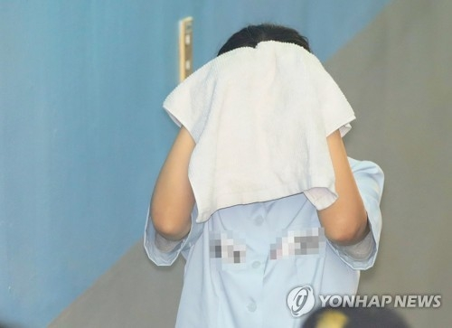 Choi You-jeong, a judge-turned-lawyer convicted of bribery charges in a high-profile lobbying scandal, walks her way into the courthouse covering her face with a towel for an appeals trial in Seoul on July 21, 2017. (Yonhap)