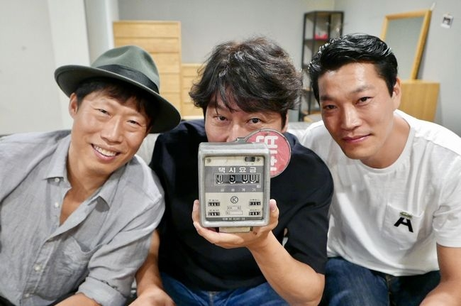 "In this photo released by Showbox, three members of the main cast of ""A Taxi Driver"" -- Yoo Hae-jin, Song Kang-ho and Choi Gui-hwa (L to R) -- pose for the camera in celebration of the film attracting over 5 million viewers. (Yonhap)"