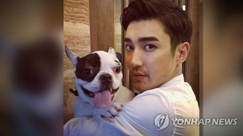 This undated photo captured from Super Junior member Choi Si-won's social media shows the star posing for the camera while holding his family pet dog. (Yonhap)