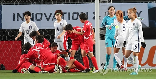 North Korea women's national football team players (in red) celebrate after scoring a goal against South Korea at the East Asian Football Federation (EAFF) E-1 Football Championship at Soga Sports Park in Chiba, Japan, on Dec. 11, 2017. (Yonhap)