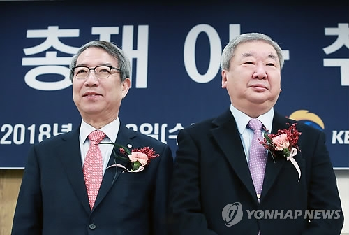 Koo Bon-neung (R), outgoing commissioner of the Korea Baseball Organization, stands next to new commissioner, Chung Un-chan, during the latter's inauguration ceremony in Seoul on Jan. 3, 2018. (Yonhap)