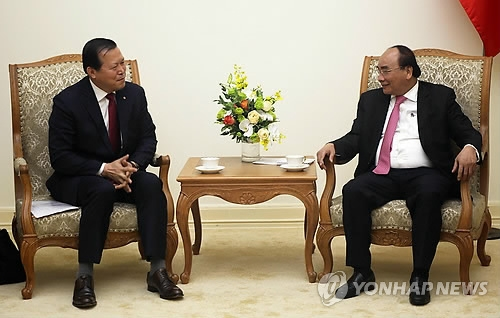In this photo provided by Lotte Corp., the holding firm of South Korean retail giant Lotte, its chief executive Hwang Kag-gyu (L) meets with Vietnamese Prime Minister Nguyen Xuan Phuc in Hanoi on March 8, 2018. (Yonhap)