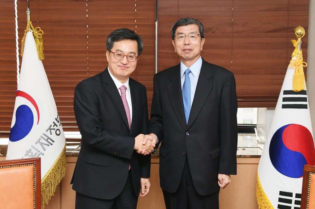 South Korea's finance minister Kim Dong-yeon (L) shakes hands with Takehiko Nakao, president of the Asian Development Bank (ADB) in Seoul on March 13, 2018. (Yonhap)