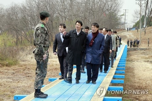 This file photo taken on April 6, 2018, shows Im Jong-seok (third from L), chief of staff to South Korean President Moon Jae-in, and other officials inspecting the footbridge on the South Korean side of the border truce village of Panmunjom in preparations for Moon's upcoming summit with North Korean leader Kim Jong-un. On April 26, 2018, one day before the summit, Im said the two leaders will jointly walk the bridge during a friendship event. (Yonhap)