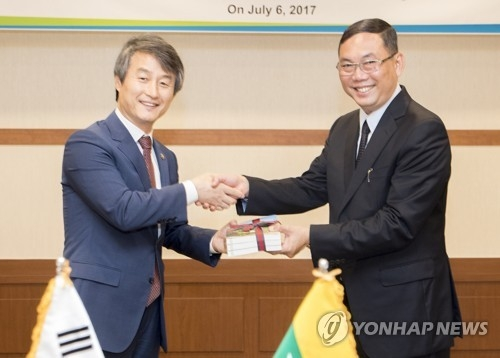 In this July 2017 file photo, released by the environment ministry, South Korean Vice Environment Minister Ahn Byung-ok (L) and U Khin Maung Yi, Myanmar's Permanent Secretary of Natural Resources and Environmental Conservation, pose for a photo during their meeting in Seoul. (Yonhap)