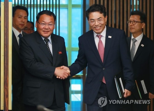This photo provided by joint press corps shows South Korea's chief delegate Kim Jeong-ryeol (R) shaking hands with his North Korean counterpart Kim Yun-hyok before starting talks on railway cooperation at the truce village of Panmunjom on June 26, 2018. (Yonhap)