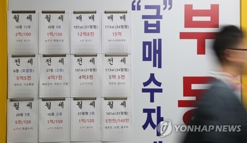 In this file photo taken Oct. 8, 2017, a passerby walks in front of a realtor's office displaying signs for home leases and home sales. (Yonhap)