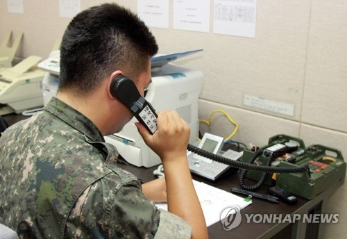 This file photo, taken in September 2013, shows a South Korean solider using a western inter-Korean military communication line. (Yonhap)