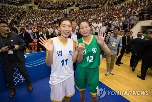 In this Joint Press Corps photo from July 4, 2018, Lim Yung-hui of South Korea (L) and Ro Suk-yong of North Korea hold hands after their friendly basketball game at Ryugyong Chung Ju-yung Gymnasium in Pyongyang. (Yonhap)