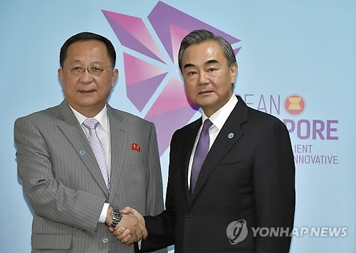 This AP photo shows Chinese Foreign Minister Wang Yi (R) shaking hands with North Korean Foreign Minister Ri Yong-ho at a Singapore meeting on Aug. 3, 2018. (Yonhap)