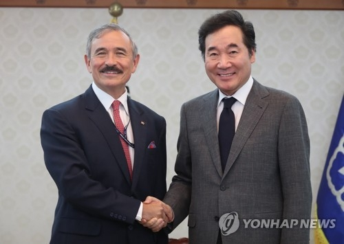 Prime Minister Lee Nak-yon (R) shakes hands with U.S. Ambassador Harry Harris during a meeting in Seoul on Aug. 8. (Yonhap)