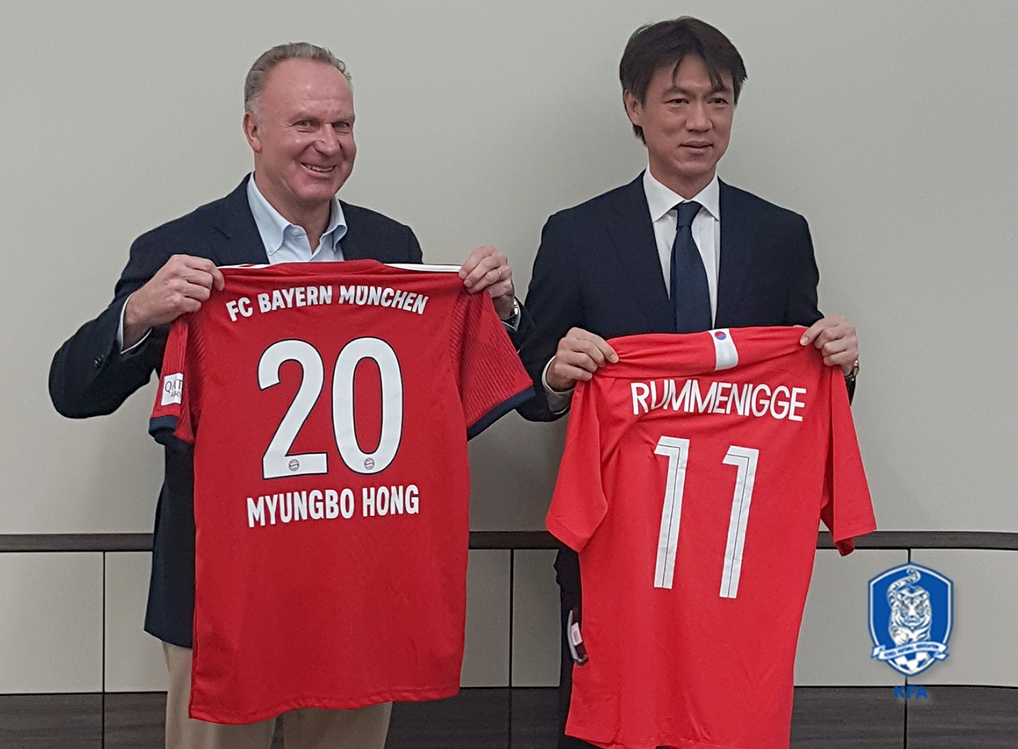 This undated photo provided by the Korea Football Association (KFA) shows Karl-Heinz Rummenigge (L), the CEO of Bayern Munich, and Hong Myung-bo, the KFA General Secretary, holding football jerseys. (Yonhap)