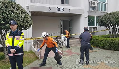 Police and firefighters inspect the scene of a fire and murders at an apartment building in Jinju, southeastern South Korea, on April 17, 2019. (Yonhap)