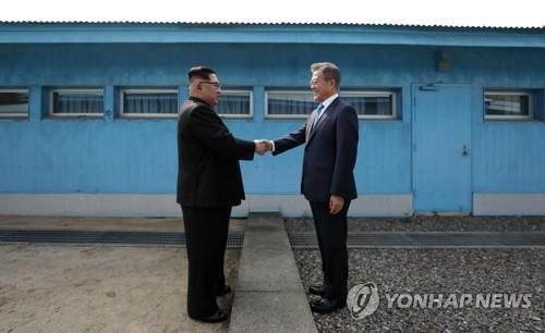This file photo shows South Korean President Moon Jae-in (R) and North Korean leader Kim Jong-un shaking hands at the peace village of Panmunjom on April 27, 2018. (Yonhap)