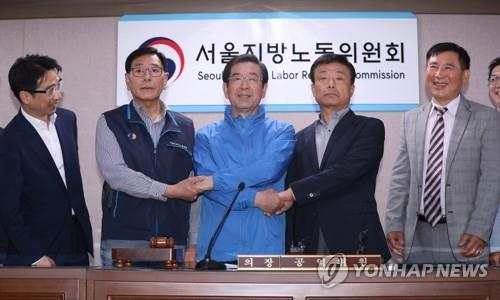 Seo Jong-su (2nd from L), leader of the Seoul Bus Drivers Labor Union, poses for a photo with Pi Jeong-kwon (2nd from R), head of the Seoul Bus Operators Association, and Seoul Mayor Park Won-soon (C) at the Seoul Regional Labor Relations Committee on May 15, 2019, after reaching a compromise agreement with management. The agreement was reached with less than two hours left until a planned walkout by unionized bus drivers. (Yonhap)