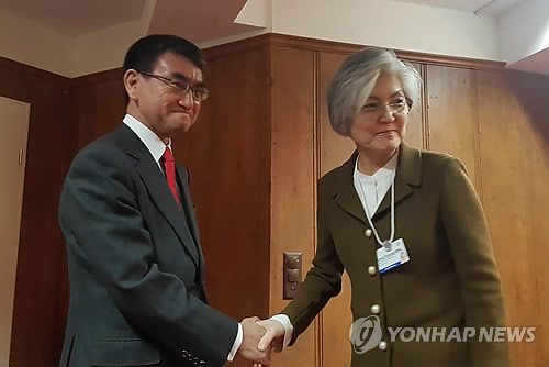 This file photo, taken Jan. 23, 2019, shows Foreign Minister Kang Kyung-wha (R) shaking hands with her Japanese counterpart, Taro Kono, before their talks on the sidelines of the World Economic Forum in Davos, Switzerland. (Yonhap)