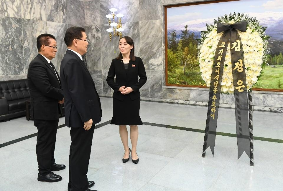 In this photo, provided by the unification ministry, North Korean leader Kim Jong-un's sister, Kim Yo-jong (R), speaks to Chung Eui-yong (C), head of South Korea's presidential National Security Office, and Rep. Park Jie-won of the minor opposition Party for Democracy and Peace at the border village of Panmunjom on June 12, 2019, beside flowers the North Korean leader is sending to the funeral of former first lady Lee Hee-ho, who died on June 10. (PHOTO NOT FOR SALE)(Yonhap)