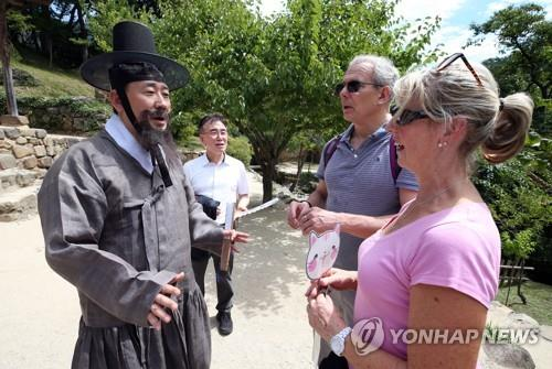 This photo provided by the Ministry of Culture, Sports and Tourism on Aug. 10, 2019, shows Minister Park Yang-woo (L) dressed in traditional Korean costume meeting foreign tourists in Damyang, South Jeolla Province, 340 kilometers south of Seoul. (PHOTO NOT FOR SALE) (Yonhap)