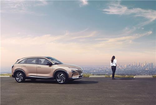 This file photo provided by Hyundai Motor shows the Nexo hydrogen fuel-cell electric car and a woman looking down a city from the road of a hill. (PHOTO NOT FOR SALE)(Yonhap)
