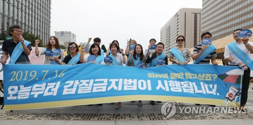This July 16, 2019, photo shows civic activists conducting a street campaign to promote a new law against workplace harassment in central Seoul. (Yonhap)
