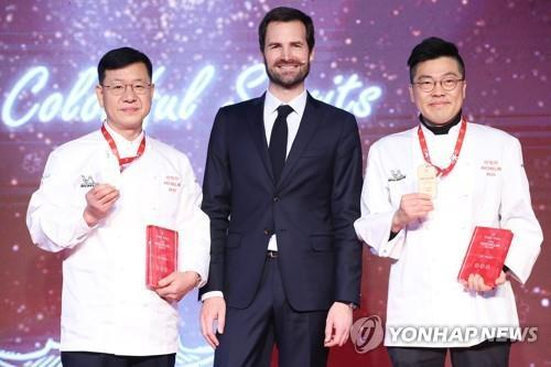 Chef Kim Byung-jin (L) from Gaon, Gwendal Poullennec (C), international director of the Michelin Guide, and Chef Kim Sung-il from La Yeon pose for a photo during an award ceremony at a Seoul hotel on Nov. 14, 2019. (Yonhap)