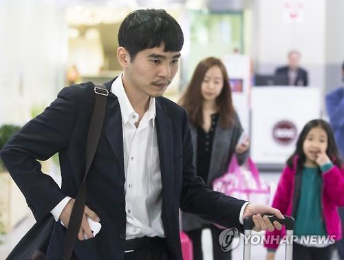 This file photo taken March 21, 2016, shows South Korean Go master Lee Se-dol (L) and his wife (C) and daughter returning to Seoul after vacationing on Jeju Island following his historic Go games against AlphaGo. (Yonhap)