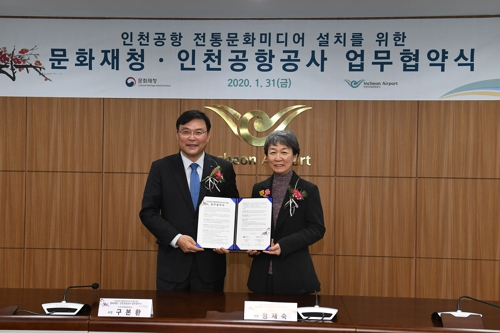 This photo provided by the Cultural Heritage Administration shows the heads of the administration and Incheon International Airport Corporation, Chung Jae-suk (R) and Koo Bon-hwan, respectively, posing for photos after signing an agreement on Jan. 31, 2020. (Yonhap)