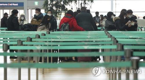 Passengers wearing face masks wait near a departure gate of Incheon International Airport, west of Seoul, on Feb. 2, 2020. (Yonhap)