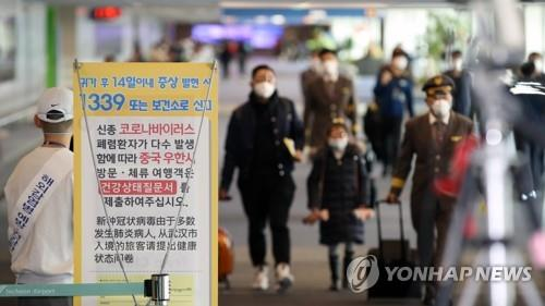 Passengers and airline crew members wearing masks approach a quarantine checkpoint at Incheon International Airport, west of Seoul, on Jan. 28, 2020, in this file photo. (Yonhap)