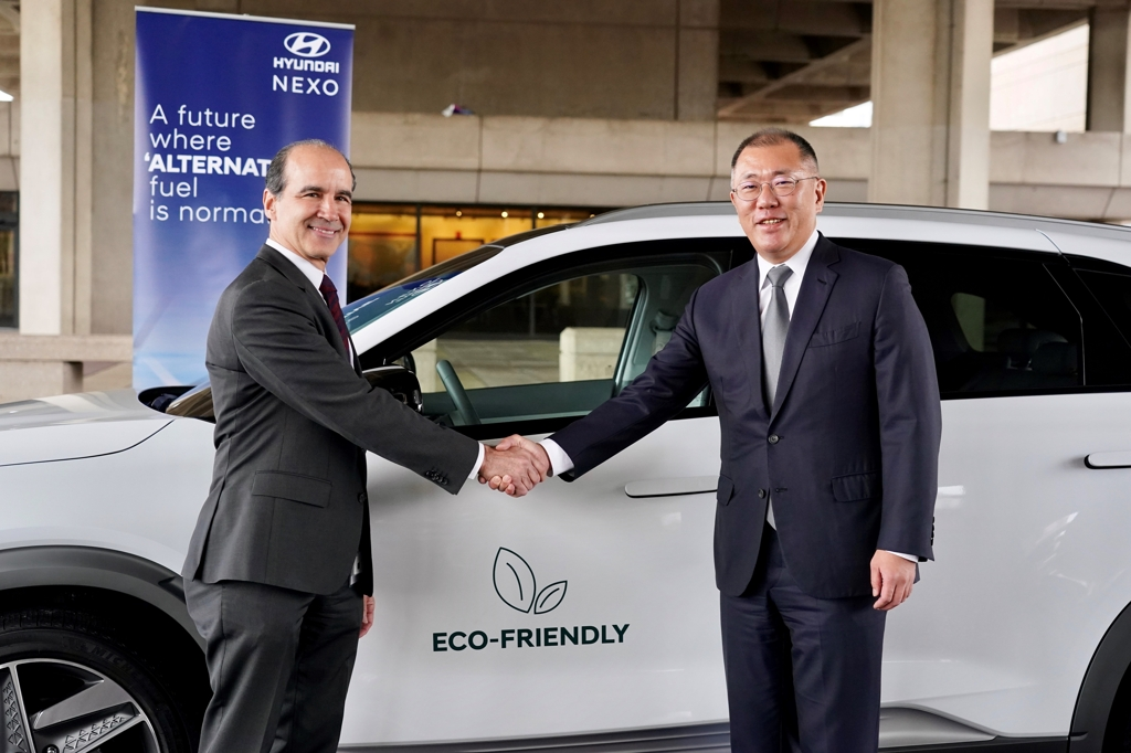 In this photo taken Feb. 10, 2020, and provided by Hyundai Motor Group, the group's Executive Vice Chairman Chung Euisun (R) shakes hands with Under Secretary of Energy Mark W. Menezes against the background of the Nexo hydrogen car in front of the energy department building in Washington, D.C. (PHOTO NOT FOR SALE) (Yonhap)