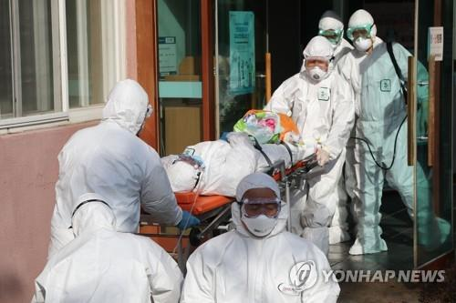 Medical workers transfer a suspected coronavirus patient from Daenam Hospital in Cheongdo, 320 kilometers southeast of Seoul, to another hospital on Feb. 21, 2020. Of about 600 patients and medical staff at the hospital, 16 tested positive for COVID-19, health authorities said. (Yonhap)