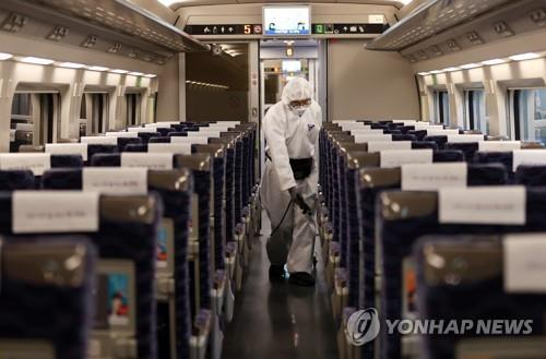 Quarantine officials disinfect a cabin of a KTX bullet train at Suseo Station in Seoul on Feb. 25, 2020, amid the spread of the new coronavirus in the country. (Yonhap)