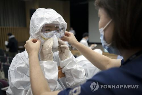 Medical staffers at Seoul Medical Center in Seoul practice wearing protective gear on Feb. 27, 2020, ahead of the center's upcoming change from being a general hospital to a COVID-19-only one, in this photo provided by the clinic. (Yonhap)