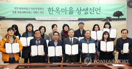 This file photo shows landlords of Jeonju Hanok Village posing with a written agreement to cut rents by up to 20 percent. (Yonhap)