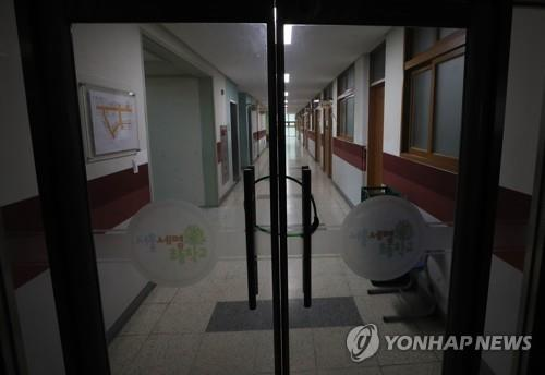An entrance door is locked at Semyung Elementary School in southern Seoul on March 2, 2020. The school had originally planned to resume the spring semester on the day but postponed its start in accordance with the government's efforts to curb the coronavirus outbreak. (Yonhap)