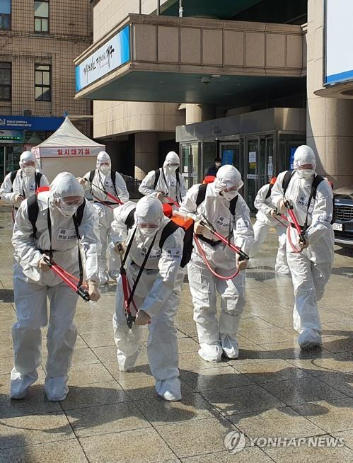 Soldiers disinfect the ground outside City Hall in the southeastern city of Daegu, the epicenter of the coronavirus outbreak in South Korea, on March 2, 2020. (Yonhap)